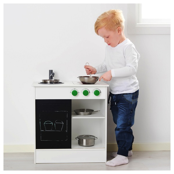 menino mexendo panela cozinha de brinquedo